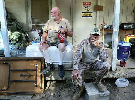 "Landowner Cuban ""Rusty"" Monsees sits with the cigarette-smoking KC Massey. Monsees invited the armed civilians who call themselves ""American Patriots"" onto his property along the Rio Grande."