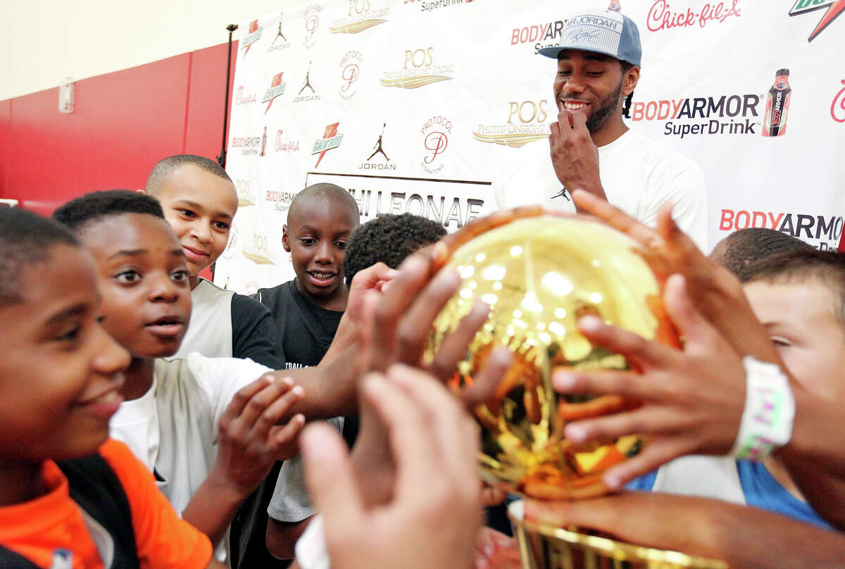 San Antonio Spurs' Kawhi Leonard (center rear) laughs as children touch the Larry O'Brien NBA Championship Trophy during the third annual Kawhi Leonard Basketball Skills Clinic held Saturday Aug. 9, 2014 at the Moreno Valley Conference & Recreation Center in Moreno Valley, CA.