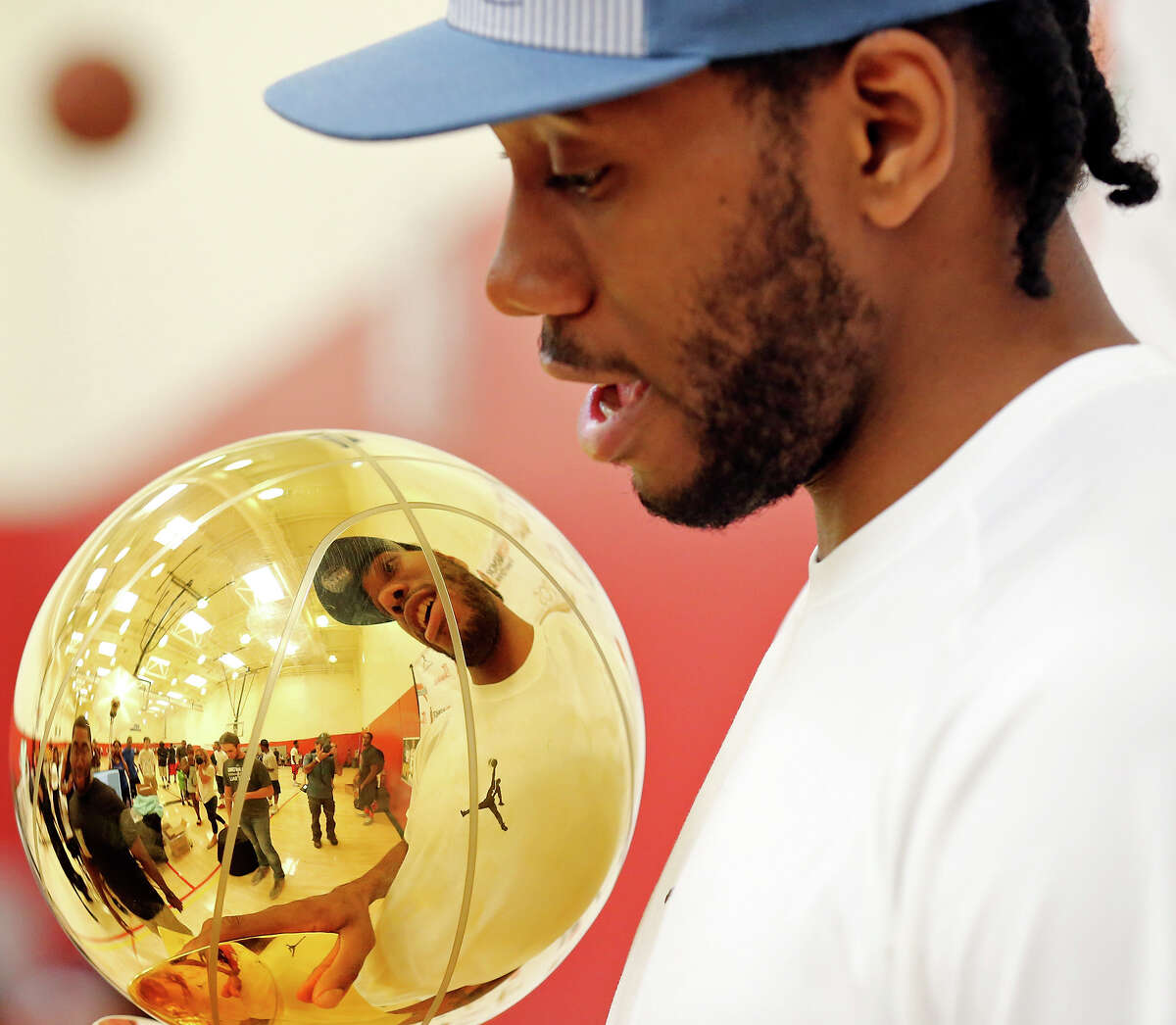 San Antonio Spurs' Kawhi Leonard is reflected in the Larry O'Brien NBA Championship Trophy during the third annual Kawhi Leonard Basketball Skills Clinic held Saturday Aug. 9, 2014 at the Moreno Valley Conference & Recreation Center in Moreno Valley, CA.