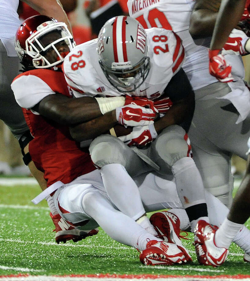 UNLV running back Keith Whitley, right, is tackled for a loss by Houston linebacker Steven Taylor during the first half of an American Athletic Conference college football game, Saturday, September 20, 2014, at TDECU Stadium in Houston. (Photo: Eric Christian Smith/For the Chronicle) Photo: Eric Christian Smith, Freelance / 2014 Eric Christian Smith