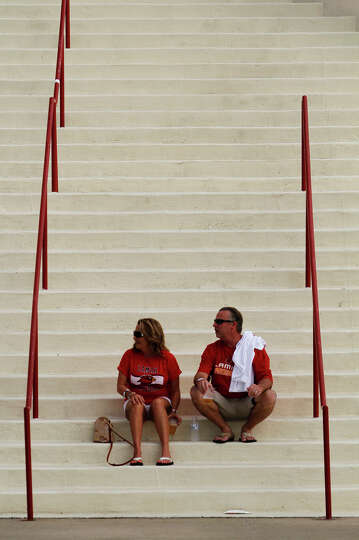Jeanne and Scott Guidry sit on the steps of the Montagne Center before Saturday's football game. The