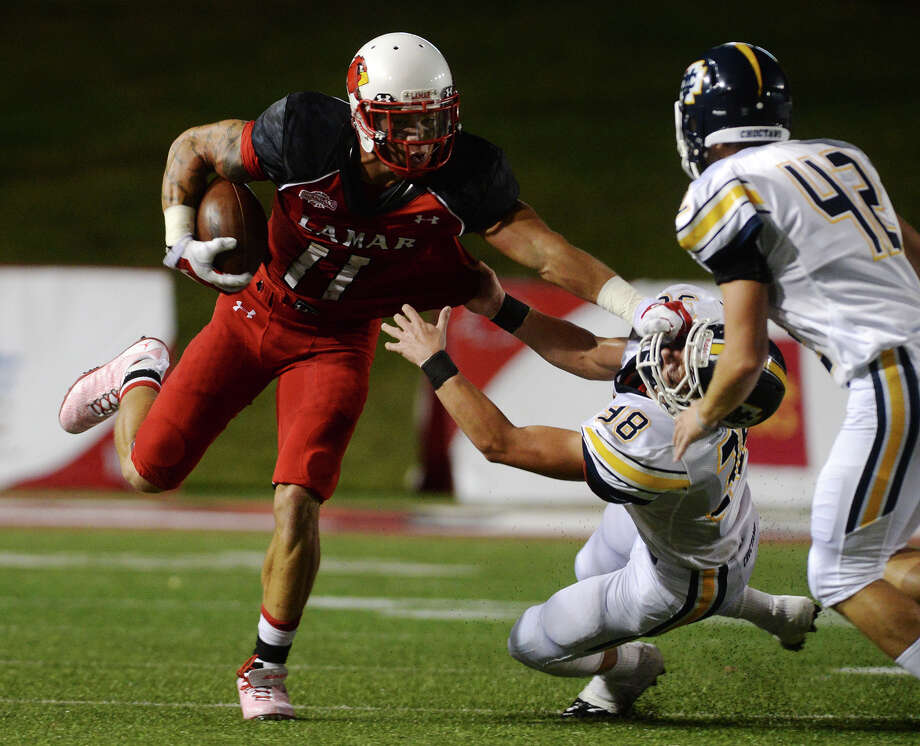 Lamar's Kevin Johnson, No. 11, holds off Mississippi College's Trace Lane, No. 38, as he returns a punt during Saturday's game. The Lamar Cardinals hosted the Mississippi College Choctaws at Provost Umphrey Stadium on Saturday night.  Photo taken Saturday 9/20/14  Jake Daniels/@JakeD_in_SETX Photo: Jake Daniels / ©2014 The Beaumont Enterprise/Jake Daniels