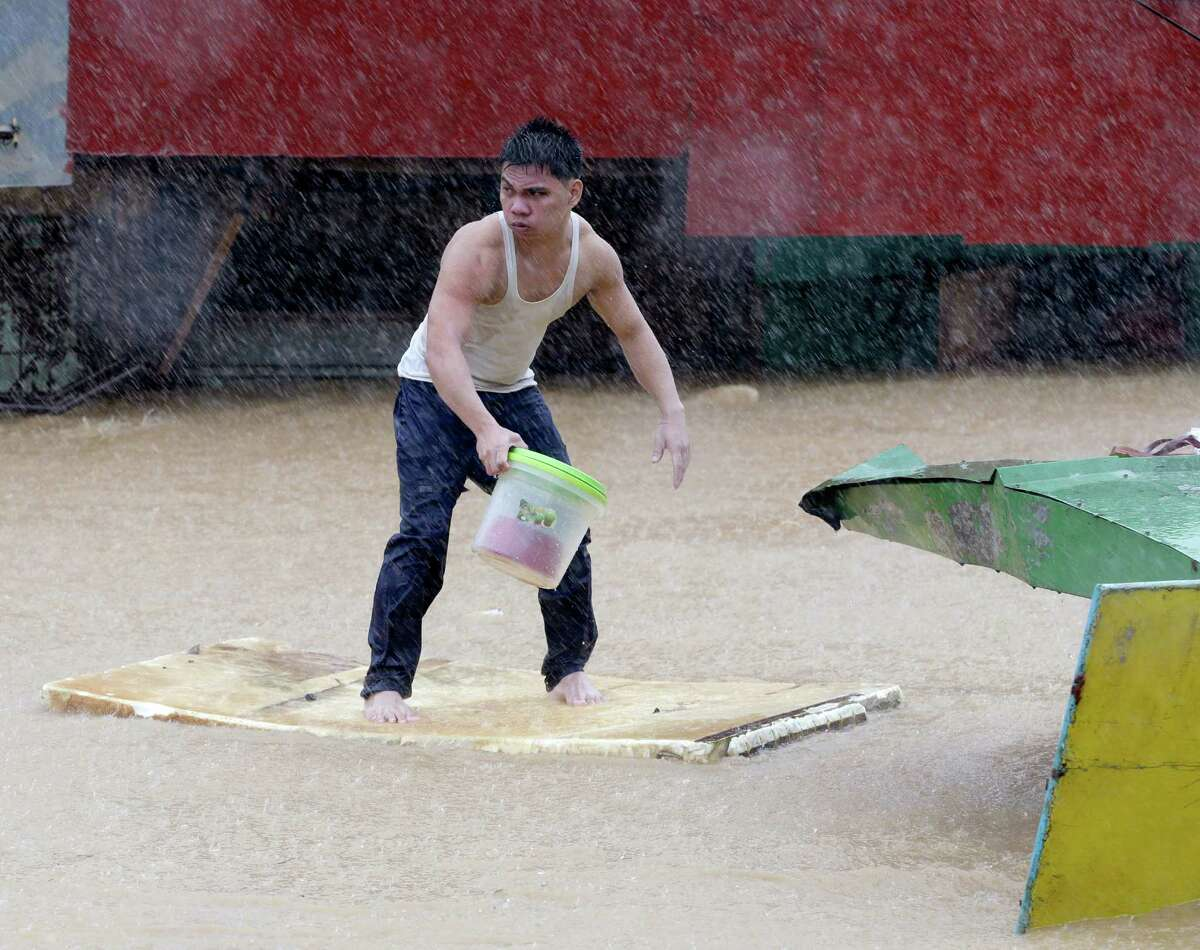 A resident balances himself on a makeshift floater as he evacuates to safety after heavy monsoon rains spawned by tropical storm Fung-Wong flooded Marikina city, east of Manila, Philippines and most parts of the metropolis Friday, Sept.19, 2014. Heavy rains due to a storm and the seasonal monsoon caused widespread flooding Friday in the Philippine capital and nearby provinces, shutting down schools and government offices.