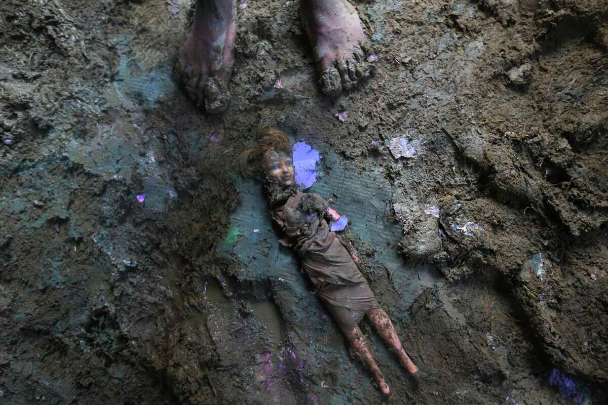 A Kashmiri stands near a doll smeared with mud inside a flood damaged house in Srinagar, India, Friday, Sept. 19, 2014. The floods engulfed much of Kashmir two weeks ago, leaving hundreds of thousands of people homeless in both the Indian- and Pakistani-administered areas of the disputed territory.Latest AP headline: Doctors: Foul floodwaters sicken people in Kashmir