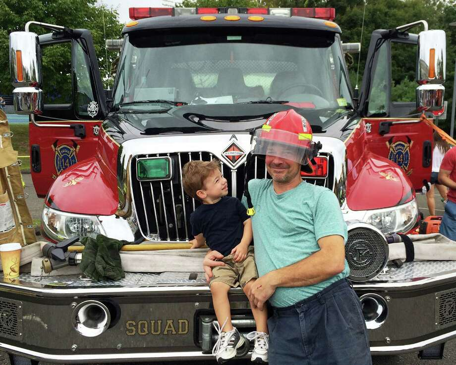 Brian Furrer, 2, and dad, Fenton, get a small taste of what it's like to be a firefighter as they checked out one of the fire trucks on display Sunday at the annual Touch-a-Truck event sponsored by the Fairfield Junior Women's Club. Photo: Stephanie Borise / Fairfield Citizen