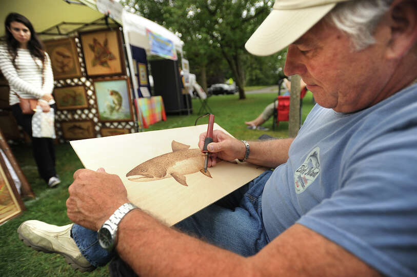 Wood burning artist John Houle, of Hamden, works on a rainbow trout piece outside his booth at the 2