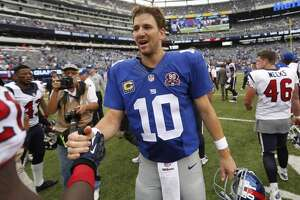 New York Giants quarterback Eli Manning walks off the field after his Giants beat the Houston Texans in an NFL football game at MetLife Stadium on Sunday, Sept. 21, 2014, in East Rutherford, N.J. ( Brett Coomer / Houston Chronicle )