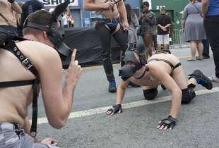 Two men dressed as dogs role play in the street during the Folsom Street Fair in San Francisco, Calif. on September 21, 2014.