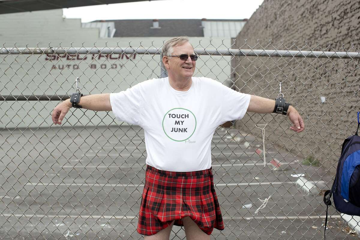 A man is chained to the fence with a shirt that reads,