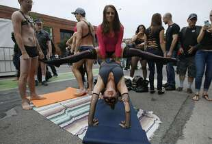 Kendra Charts of Chicago (top) performs an acrobatics routine with Mara Saunders of Berkeley during the Folsom Street Fair in San Francisco, Calif. Sunday, September 21, 2014.