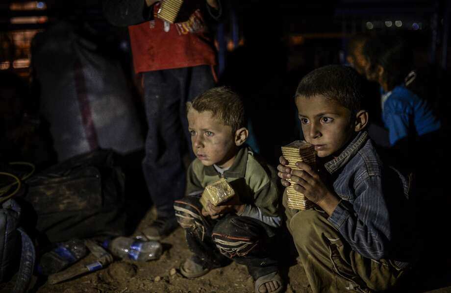 Syrian Kurdish children wait after crossing the Turkish border near the southeastern town of Suruc in Sanliurfa province. Photo: BULENT KILIC, Staff / AFP/Getty Images / AFP