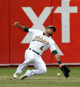 Oakland Athletics' Coco Crisp can't catch a double by Philadelphia Phillies' Ryan Howard in 3rd inning during MLB game at O.co Coliseum  in Oakland, Calif. on Sunday, September 21, 2014.