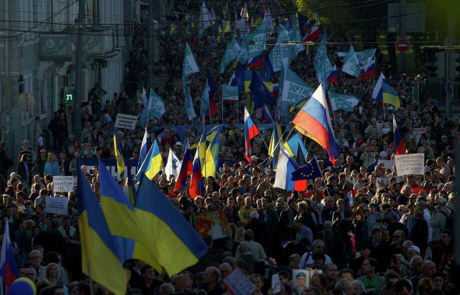 People carry Russian and Ukrainian flags during an anti-war rally in downtown Moscow, Russia, Sunday, Sept. 21, 2014. Thousands of people were marching through central Moscow to demonstrate against the fighting in Ukraine. (AP Photo/Denis Tyrin) Photo: Denis Tyrin, STR / Associated Press / AP