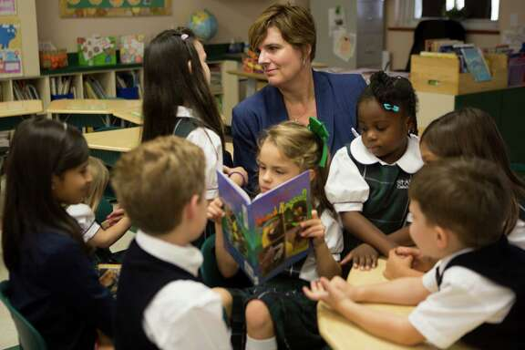 St. Anne's Catholic School's superintendent Dr. Julie Vogel interacts with students Kathleen Havens, Addison Walters, Victoria Bell, Tallulah Garza and Christian Walters, Friday, Sept. 19, 2014, in Houston. ( Marie D. De Jesus / Houston Chronicle )