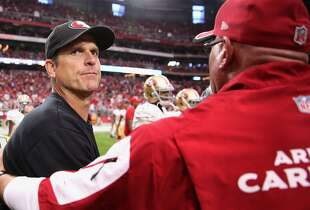 GLENDALE, AZ - SEPTEMBER 21:  Head coach Jim Harbaugh of the San Francisco 49ers shakes hands with head coach Bruce Arians of the Arizona Cardinals following the NFL game at the University of Phoenix Stadium on September 21, 2014 in Glendale, Arizona.  The Cardinals defeated the 49ers 23-14.  (Photo by Christian Petersen/Getty Images)