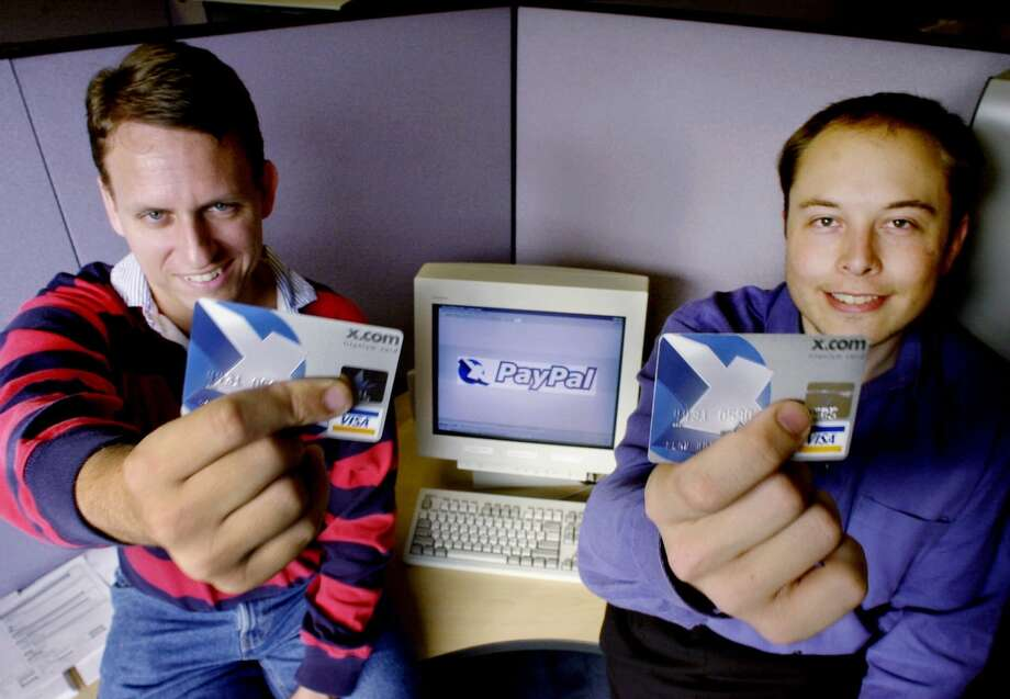 Peter Thiel (left) and Elon Musk, X.Com Corp. chairman and CEO respectively, show the cards they use for what became PayPal in 2000. The initial goal was to create an Internet currency to replace the dollar. Photo: PAUL SAKUMA / PAUL SAKUMA / Associated Press 2000