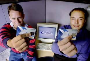 Peter Thiel (left) and Elon Musk, X.Com Corp. chairman and CEO respectively, show the cards they use for what became PayPal in 2000. The initial goal was to create an Internet currency to replace the dollar.