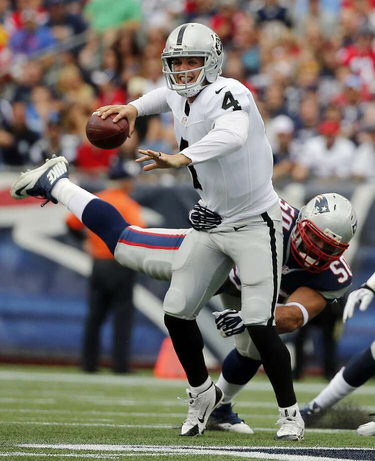 New England Patriots defensive end Rob Ninkovich (50) tries to take down Oakland Raiders quarterback Derek Carr (4) in the first half of an NFL football game Sunday, Sept. 21, 2014, in Foxborough, Mass. (AP Photo/Elise Amendola) Photo: Elise Amendola, Associated Press