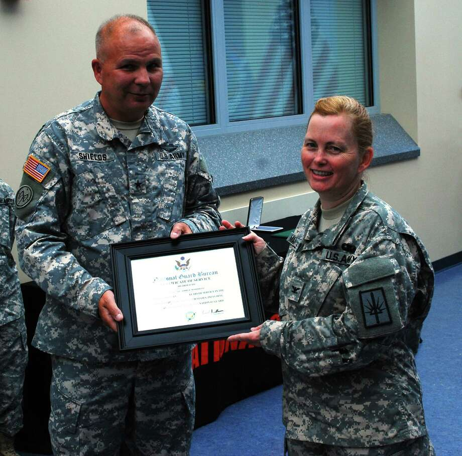 Brig. Gen. Raymond Shields, Director of Joint Staff for the New York National Guard presents Col. Tammy Mandwelle, of Queensbury, with her retirement certificate during a ceremony.