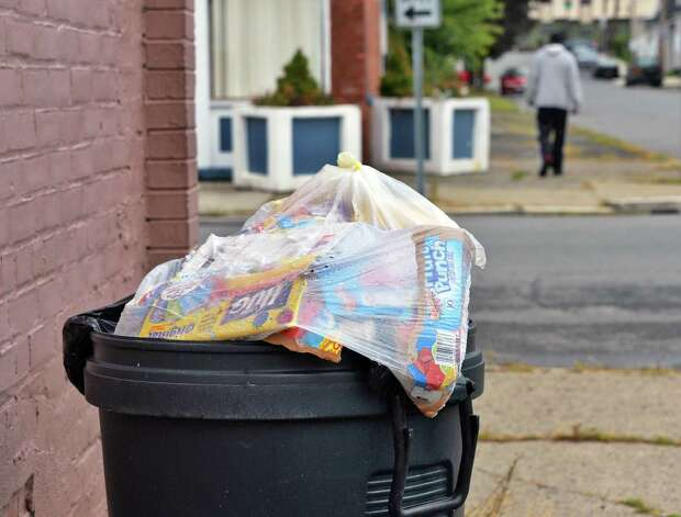 An uncovered and overflowing trash can along Jackson Street Tuesday Sept. 16, 2014, in Troy, NY.  (John Carl D'Annibale / Times Union) Photo: John Carl D'Annibale / 00028621A