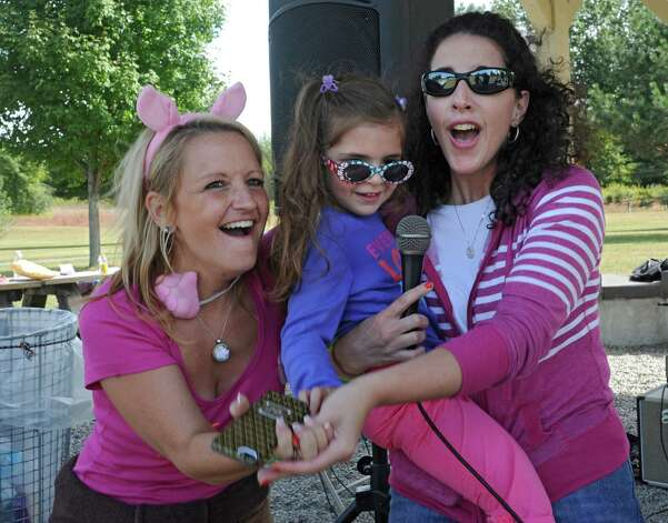 "From left, Missy Riley of Florida, Rachel D'Onofrio, 3 of Mechanicville and her mom Dana D'Onofrio sing Bon Jovi's ""Living On a Prayer"" at The Albany Walk for Farm Animals at The Crossings of Colonie on Sunday, Sept. 21, 2014 in Colonie, N.Y. For more than 25 years, Farm Sanctuary has rescued and provided sanctuary for abused farm animals, educated the public about the routine cruelty they endure on factory farms, and advocated on their behalf. The Walks bring together thousands of people from different backgrounds in cities all across the U.S. and Canada to raise vital funds to support the organizationOs life-saving work and promote kindness towards farm animals. (Lori Van Buren / Times Union) Photo: Lori Van Buren / 00028631A"