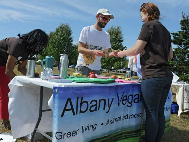 Registered Dietitian Eric Sharer sells a shopping bag to Ashley Snyder of Syracuse as he works at the Albany Vegan Network table at The Albany Walk for Farm Animals fundraiser at The Crossings of Colonie on Sunday, Sept. 21, 2014 in Colonie, N.Y. For more than 25 years, Farm Sanctuary has rescued and provided sanctuary for abused farm animals, educated the public about the routine cruelty they endure on factory farms, and advocated on their behalf. The Walks bring together thousands of people from different backgrounds in cities all across the U.S. and Canada to raise vital funds to support the organizationOs life-saving work and promote kindness towards farm animals. (Lori Van Buren / Times Union) Photo: Lori Van Buren / 00028631A