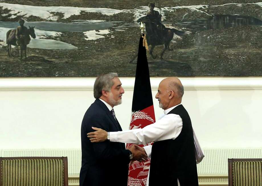Afghan presidential candidates Abdullah Abdullah, left, and Ashraf Ghani Ahmadzai, right, shake hands after signing a power-sharing deal Sunday. Photo: Massoud Hossaini, STF / AP