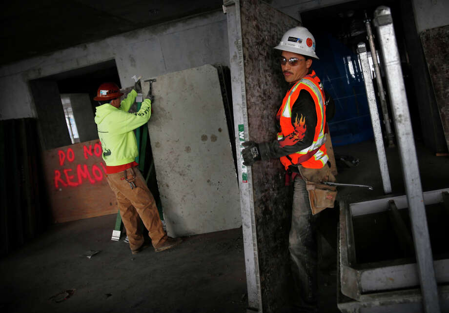 Diego Vaca (left) works on the 23rd floor of the Beale Street tower of the Lumina development. The four-building Lumina will test the upper echelons of San Francisco's housing market. Photo: Lea Suzuki, Staff / The Chronicle / ONLINE_YES