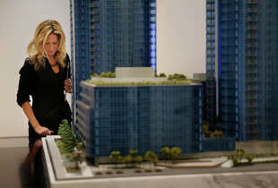 Jessica Keenan, Lumina sales associate, uses a work station next to a model of the Tishman Speyer building at the sales gallery in downtown San Francisco.