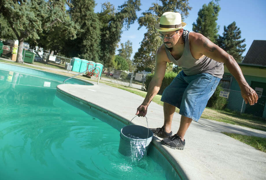 Sal Martinez draws water out of pool Tuesday, Sept. 16, 2014 at Eagle's Nest Resort in Porterville, Calif.  The park is offering the residents pool water to flush toilets and for other non-potable uses. (AP Photo/The Porterville Recorder, Chieko Hara) Photo: Chieko Hara, MBR / the Porterville Recorder