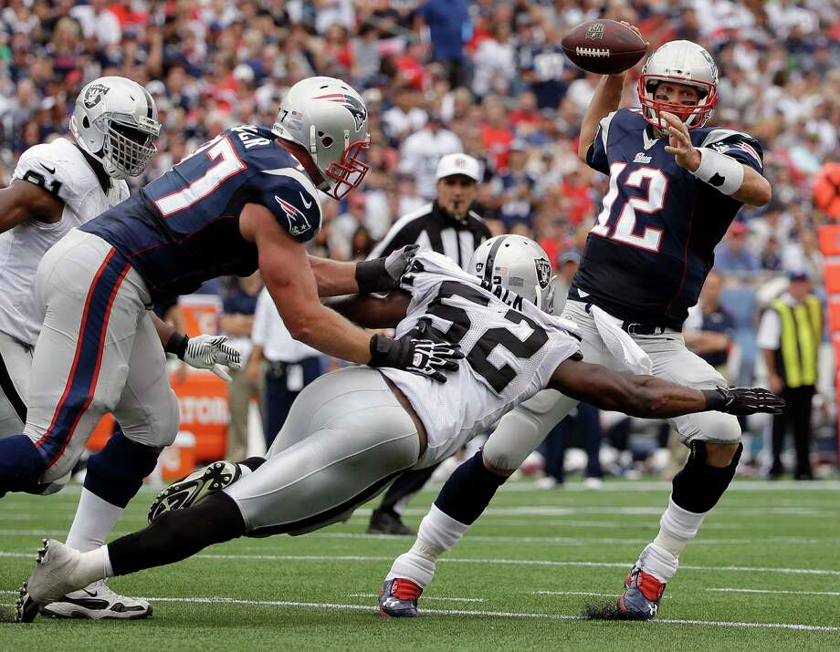 Oakland Raiders outside linebacker Khalil Mack (52) pressures New England Patriots quarterback Tom Brady (12) in the first half of an NFL football game Sunday, Sept. 21, 2014, in Foxborough, Mass. (AP Photo/Steven Senne) ORG XMIT: FBO111 Photo: Steven Senne / AP