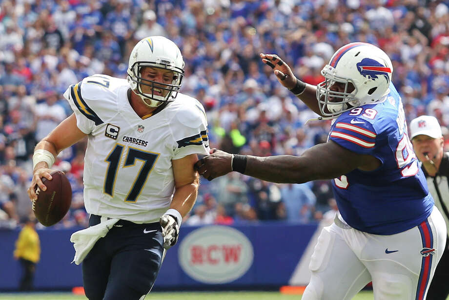 San Diego Chargers quarterback Philip Rivers (17) scrambles away from Buffalo Bills defensive tackle Marcell Dareus (99) during the first half of an NFL football game, Sunday, Sept. 21, 2014, in Orchard Park, N.Y. (AP Photo/Bill Wippert) ORG XMIT: NYFF113 Photo: Bill Wippert / FR170745 AP