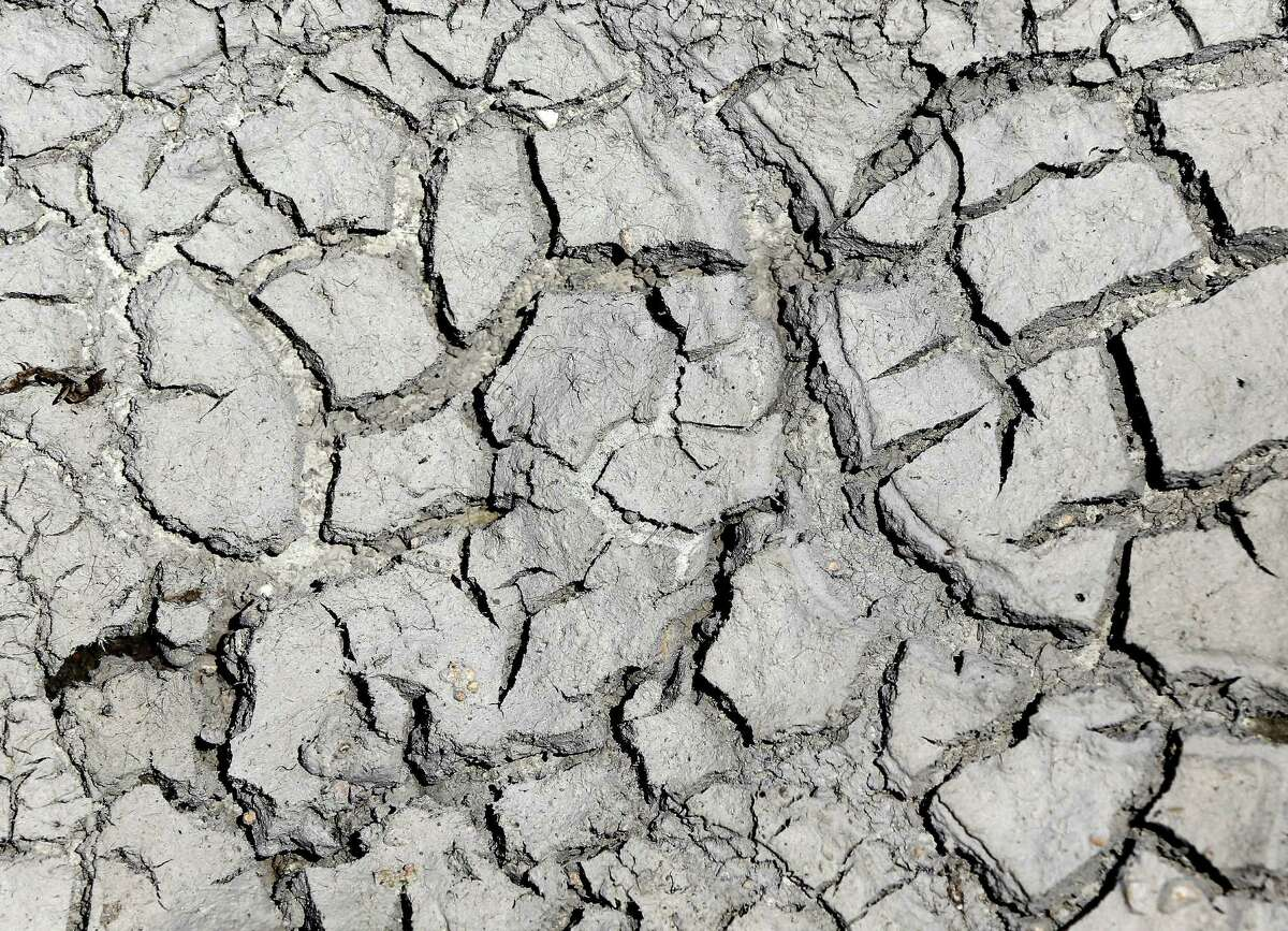 Dry, cracked, dirt is seen in the middle of the Guadalupe River which has run dry Wednesday Aug. 6, 2014 at the Rebecca Creek Road bridge crossing or nearly dry, with just .14 cubic feet per second flow rate as of the 4 p.m. reading at the Spring Branch gauge,