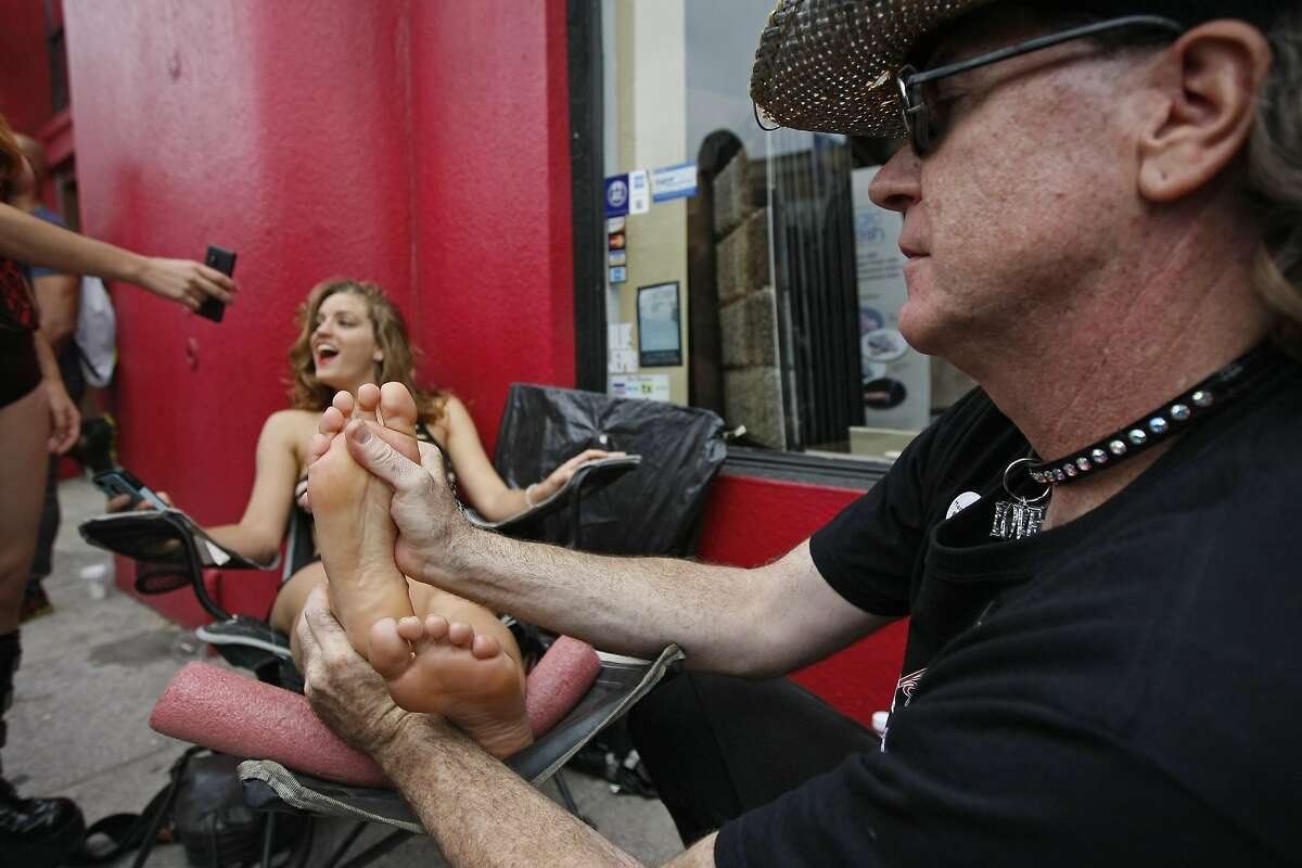 Jimi Toe Master gives a free foot massage to Courtney McElrath of San Francisco during the Folsom Street Fair in San Francisco, Calif. Sunday, September 21, 2014