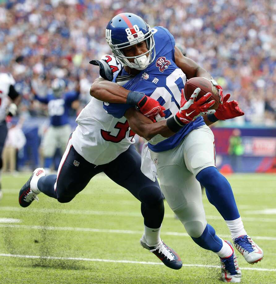New York Giants wide receiver Victor Cruz (80) is pulled down by Houston Texans cornerback A.J. Bouye (34) on his way to a touchdown in the second quarter of an NFL football game, Sunday, Sept. 21, 2014, in East Rutherford, N.J. (AP Photo/Kathy Willens)  ORG XMIT: ERU112 Photo: Kathy Willens / AP