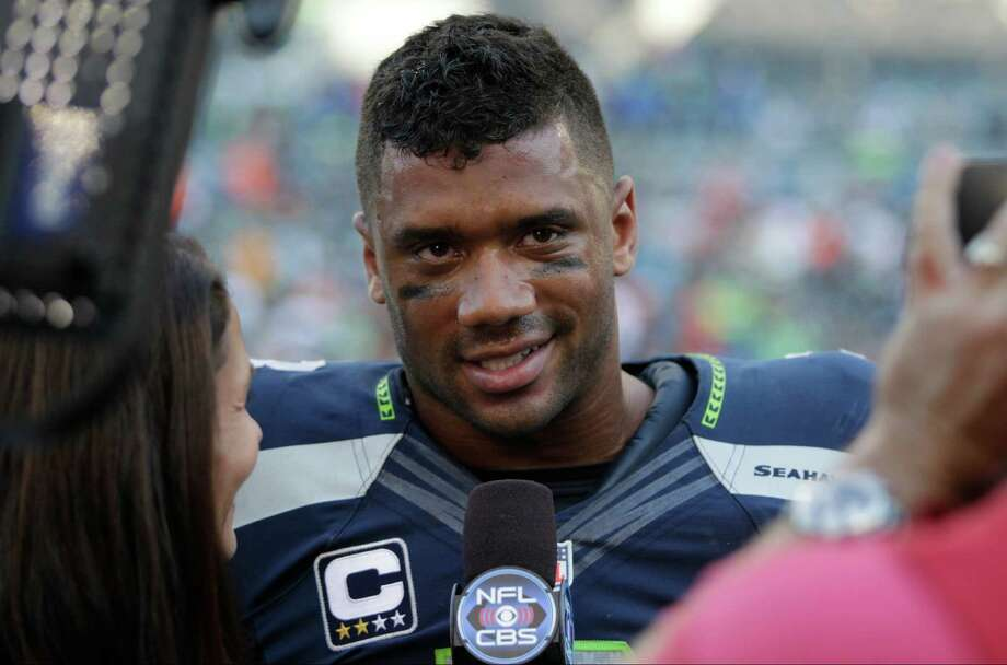 Seattle Seahawks quarterback Russell Wilson is interviewed on the field after an NFL football game, Sunday, Sept. 21, 2014, in Seattle. (AP Photo/John Froschauer) Photo: John Froschauer, FRE / FR74207 AP