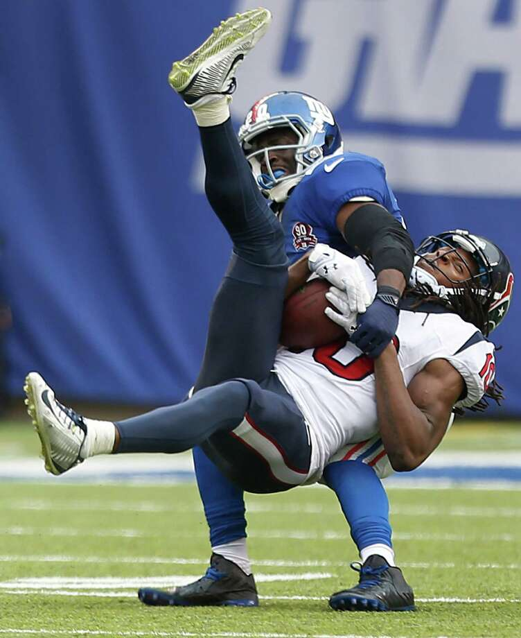 In what resembles an awkward chorus line, Texans receiver DeAndre Hopkins (10) pulls down a 49-yard reception with New York Giants cornerback Prince Amukamara defending during the fourth quarter. Photo: Brett Coomer, Staff / © 2014  Houston Chronicle