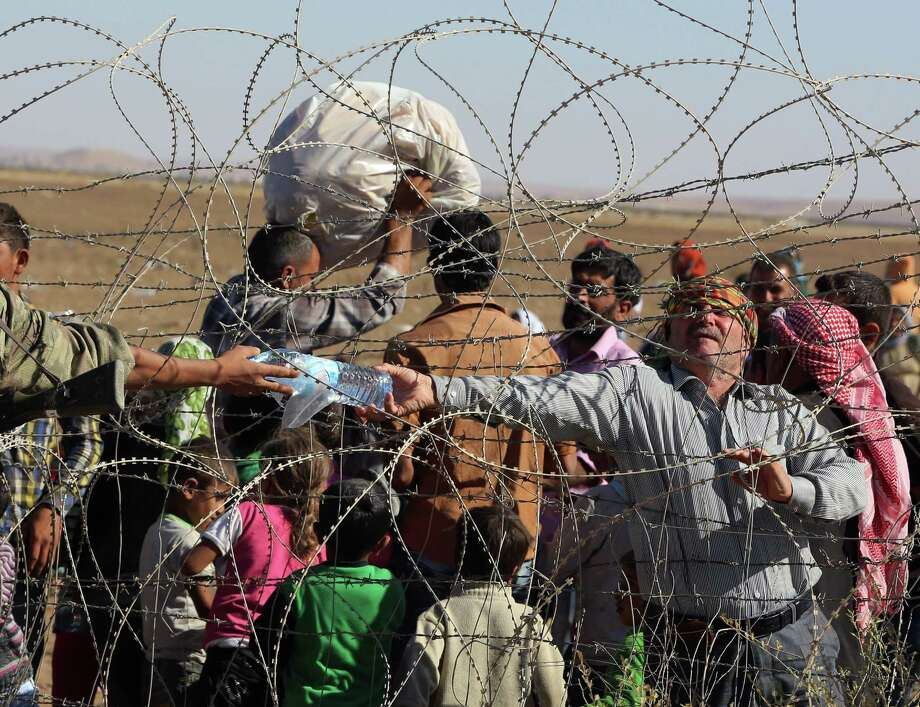 A Turkish soldier gives a bottle of water to a handicapped Syrian refugee waiting at the border in Suruc, Turkey, Sunday, Sept. 21, 2014. Turkey opened its border Saturday to allow in up to 60,000 people who massed on the Turkey-Syria border, fleeing the Islamic militants' advance on Kobani.  (AP Photo/Burhan Ozbilici) ORG XMIT: XBO150 Photo: Burhan Ozbilici / STR