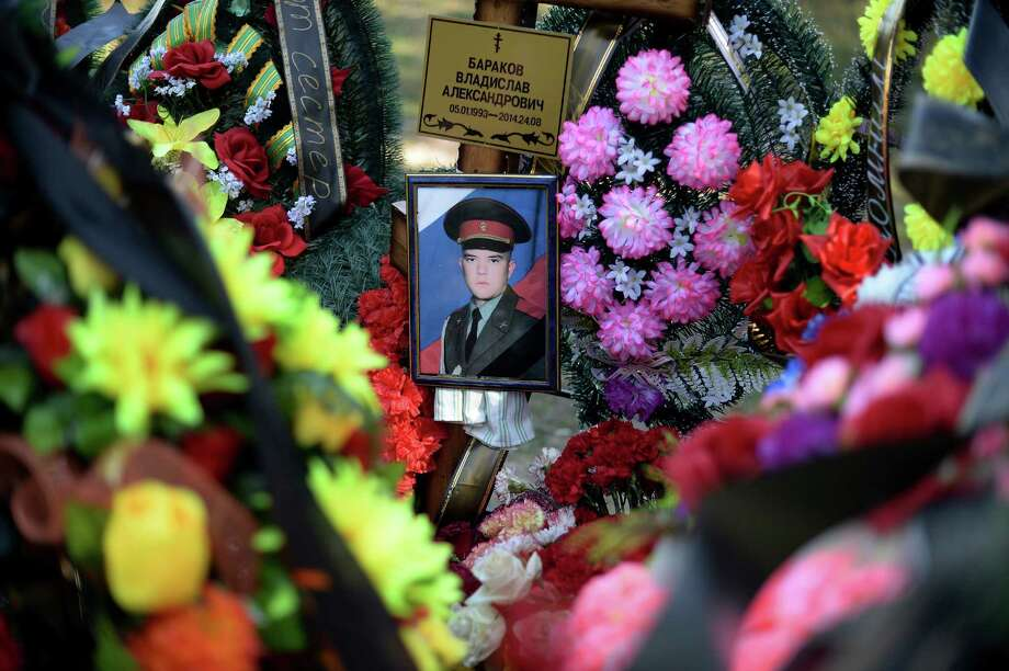 A photo of Sgt. Vladislav Barakov, who was killed in eastern Ukraine, is surrounded by flowers on his grave near Selizovo, Russia. The Kremlin has been trying to hide its involvement in Ukraine and families of dead soldiers are pressured to keep quiet. Photo: JAMES HILL, STR / NYTNS
