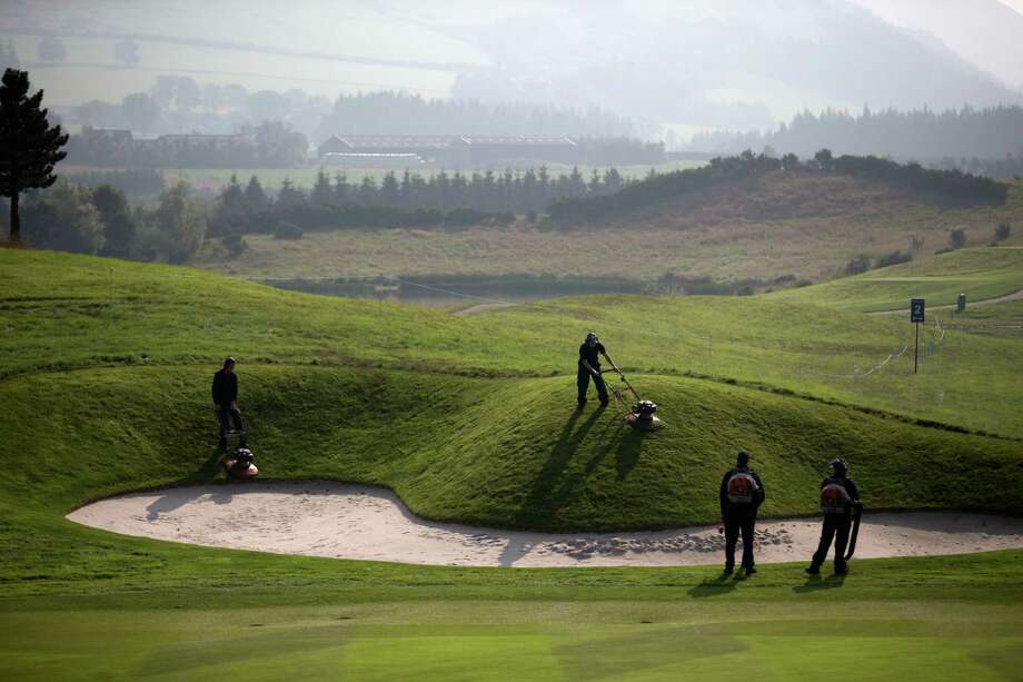 Greenskeepers work on the course in preparation for the start of the Ryder Cup golf tournament in Gleneagles, Scotland, Sunday, Sept. 21, 2014.  The U.S. team arrives for the Ryder Cup Monday, with the tournament  starting on Friday.  (AP Photo/Matt Dunham) ORG XMIT: LMD114 Photo: Matt Dunham / AP