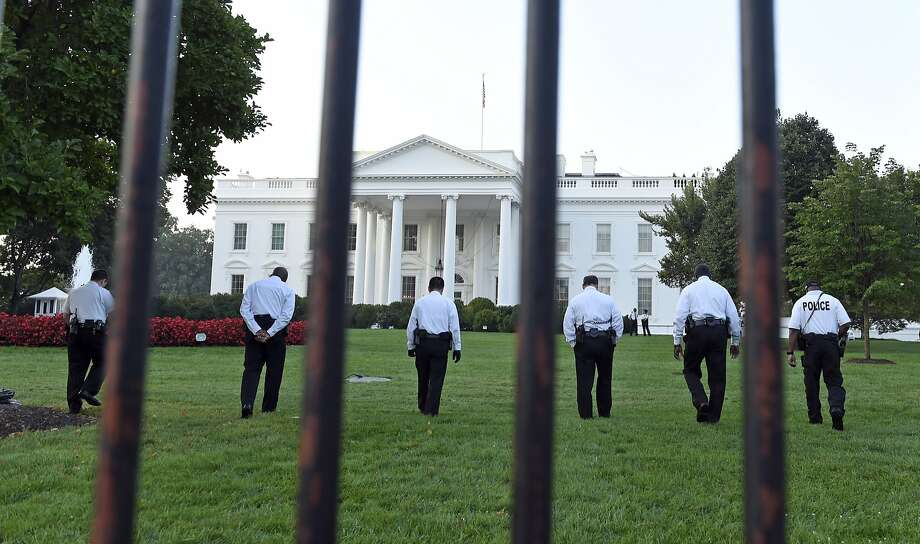 Uniformed Secret Service officers walk along the lawn on the North side of the White House in Washington, Saturday, Sept. 20, 2014. The Secret Service is coming under intense scrutiny after a man who hopped the White House fence made it all the way through the front door before being apprehended.  (AP Photo/Susan Walsh) Photo: Susan Walsh, Associated Press