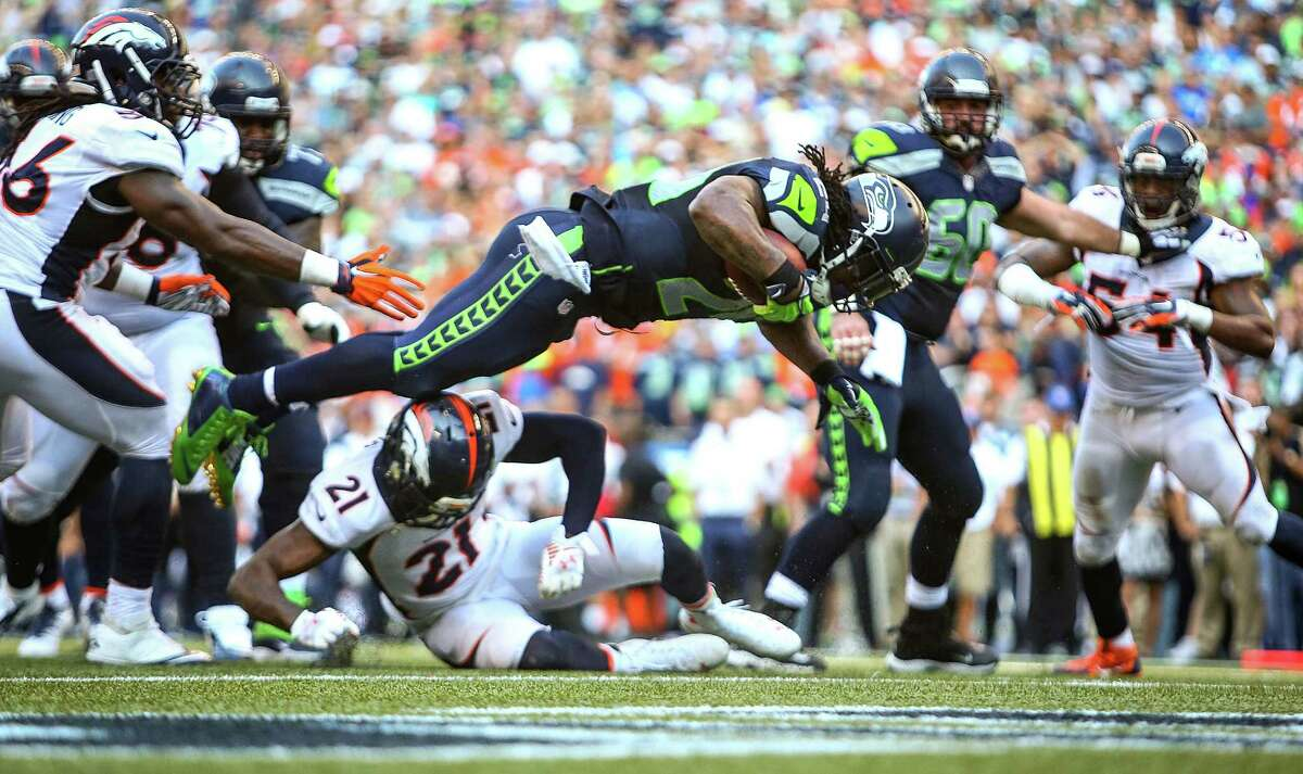 Seattle Seahawks player Marshawn Lynch flies into the endzone during a six yard run for a touchdown in overtime against the Denver Broncos on Sunday, September 21, 2014 at CenturyLink Field in Seattle. The Seahawks defeated the Broncos 26-20.