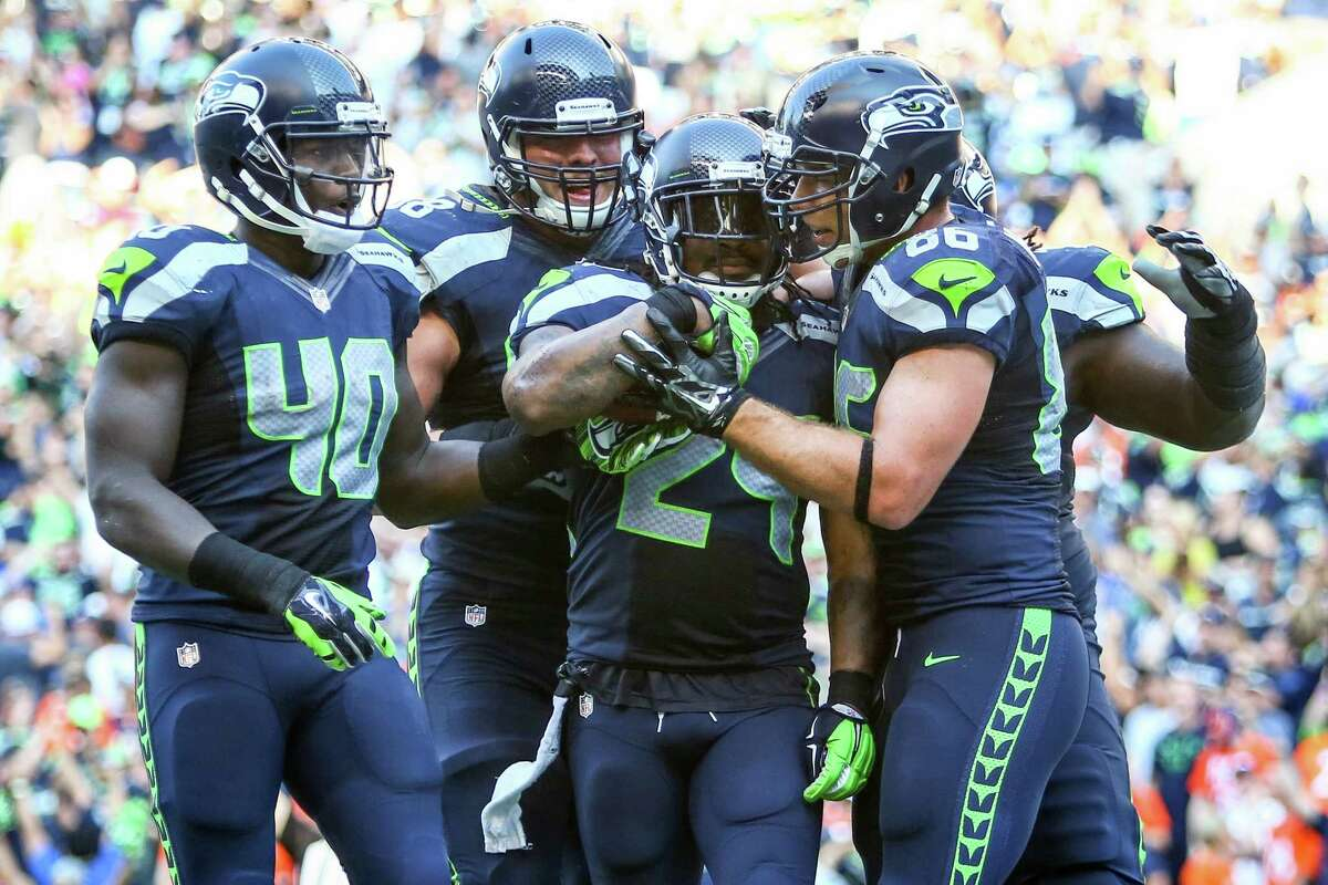 Seattle Seahawks players celebrate with Marshawn Lynch after Lynch scored a game-winning touchdown against the Denver Broncos in overtime.