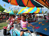 Avery Saunders, 3, of Sabine Pass waves to family as she goes for a carnival ride at the annual Pecan Festival in Groves Sunday.  Photo taken Friday, September 19, 2014 Kim Brent/@kimbpix