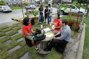 Ernesto Gutierrez, sitting left, Rosa Tang, sitting center, and Shane Bourgeois, sitting right,  all University of Houston fourth year architecture students participate in PARK(ing) Day, an annual worldwide event where artists, designers and citizens transform metered parking spots into temporary public parks, shown on campus  Friday, Sept. 19, 2014, in Houston.