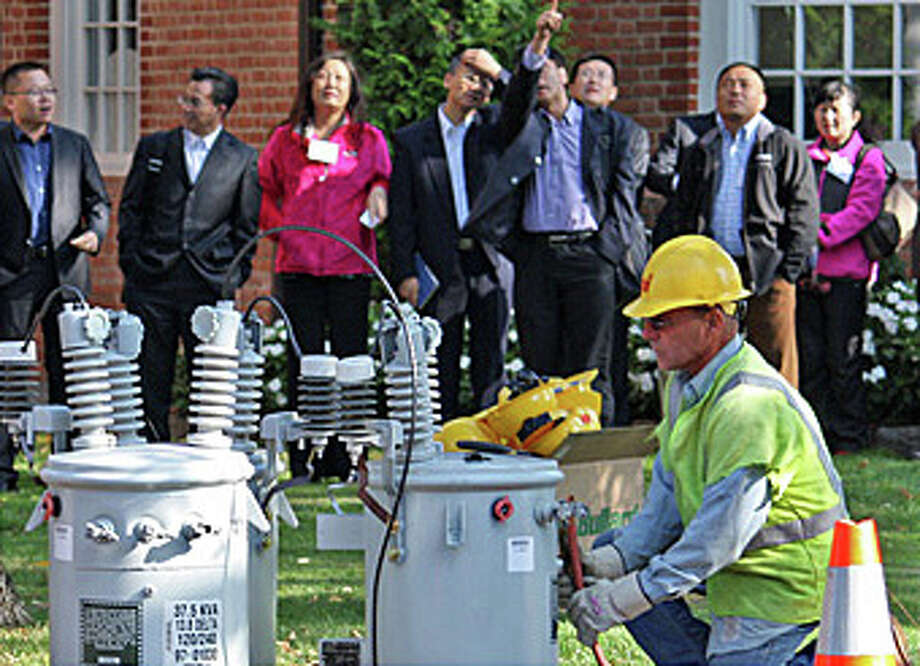 Uinted Illuminating Co. crew gives a safety demonstration to a delegation of Chinese visitors in Fairfield. Photo: Contributed Photo / Fairfield Citizen