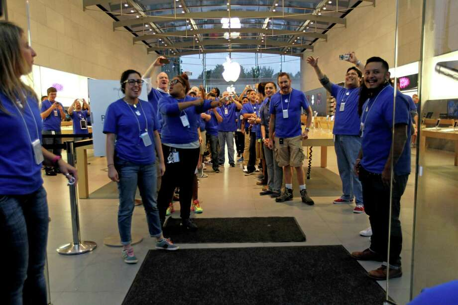 Houston employees greet customers last week for the release of Apple's iPhone 6 and iPhone 6 Plus at the Apple Store in Highland Village. On Monday, Apple said it sold more than 10 million iPhone 6 and 6 Plus models, a record for a new model, in the three days after the phones went on sale. The phones start at $199 with a two-year service contact.   Photo: Gary Coronado, Staff / © 2014 Houston Chronicle