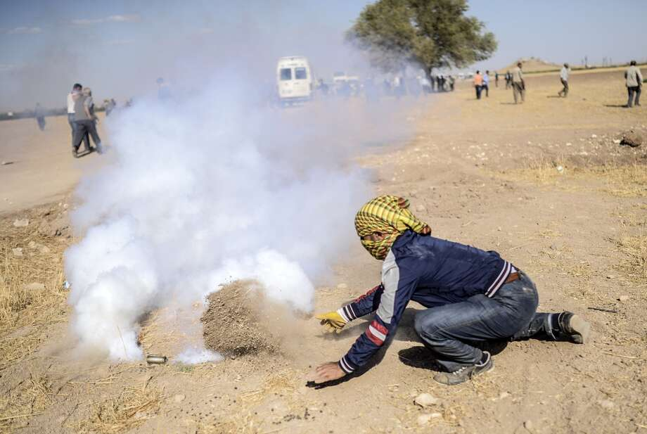 A Kurdish fighter tries to extinguish a gas canister with dirt during a clash near the Syrian border. A Kurdish tries to extinguish a gas canister with soil during clashes with Turkish soldiers (unseen) near the Syrian border after Turkish authorities temporarily closed the border near the southeastern town of Suruc in Sanliurfa province, on September 22, 2014. Turkey said on September 22 that some 130,000 people had flooded across its border from Syria as Kurdish fighters battled Islamic State group jihadists trying to capture a strategic town. Photo: BULENT KILIC, Staff / AFP/Getty Images / AFP