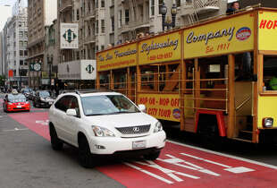 An Uber driver rides in a transit lane on Geary Street in San Francisco, a practice opposed by traditional taxi drivers.