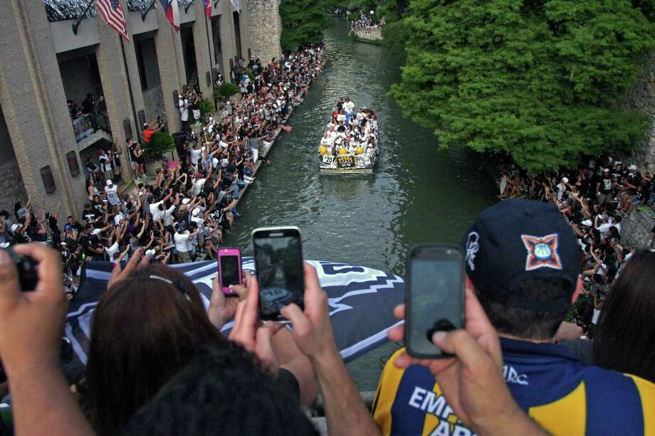 San Antonio fans record the Riverwalk boats carrying Spurs' players during the Spurs' parade and celebration of their 5th NBA Championship in San Antonio, Texas, Weds.,  June 18, 2014.  (AP Photo/Michael Thomas) Photo: Michael Thomas, Associated Press / FR65778 AP